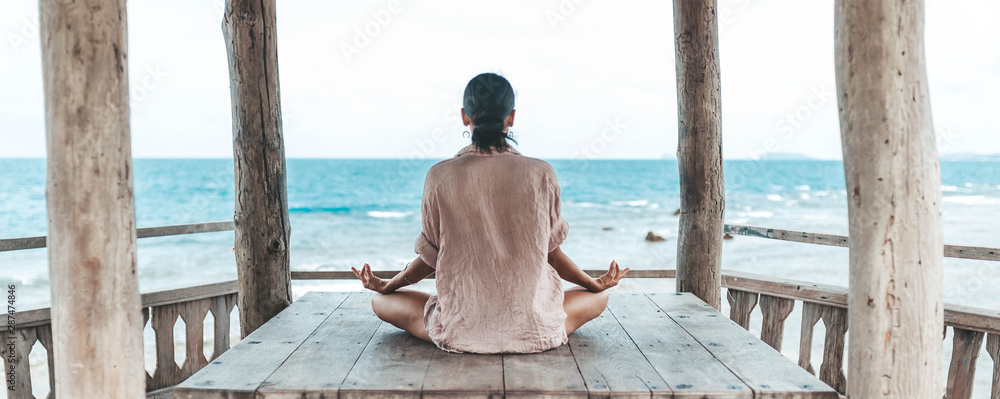 Fototapety, obrazy: young woman meditating in a yoga pose at the beach