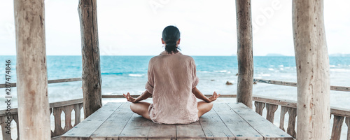 Obraz young woman meditating in a yoga pose at the beach - fototapety do salonu