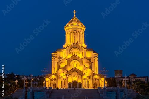 Staande foto Kiev Famous Orthodox Holy Trinitiy Sameba church illuminated with golden light.