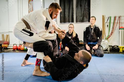 Obraz na plátně  Brazilian Jiu JItsu BJJ professor teaching technique from the guard position to