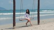 Young Beautiful Happy woman enjoying on a swing on the beach against the ocean background.