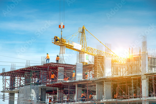 Workers are working on large construction sites and many cranes are working in the construction industry. - 287479255