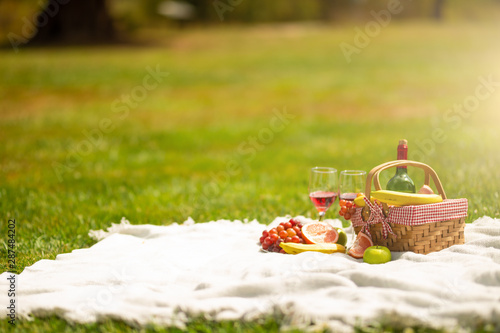 Photo sur Toile Pique-nique Picnic basket with fruit wine on a bedspread in the garden.
