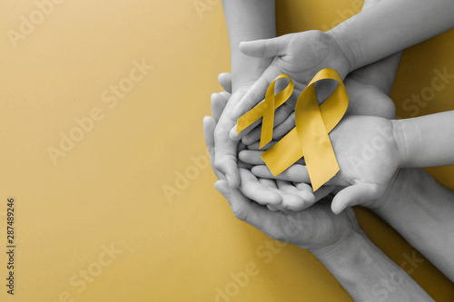 Fotomural adult and children hands holding yellow gold ribbon, Sarcoma Awareness, Bone can