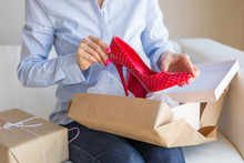 Woman Unpacking New Shoes Delivered By Post