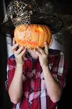 Man With A Pumpkin Instead Of A Head On A Dark Background. Pumpkin Lantern And Angled Witch Hat In Spiders - Decoration For Halloween.