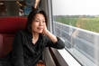 canvas print picture - Middle aged Asian woman looking out the window at landscape view sitting on train commute travel lifestyle. Mature chinese passenger traveling smiling relaxing thinking of holiday in contemplation.