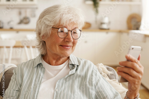 Happy joyful female pensioner in round eyeglasses surfing internet on cell phone Canvas Print
