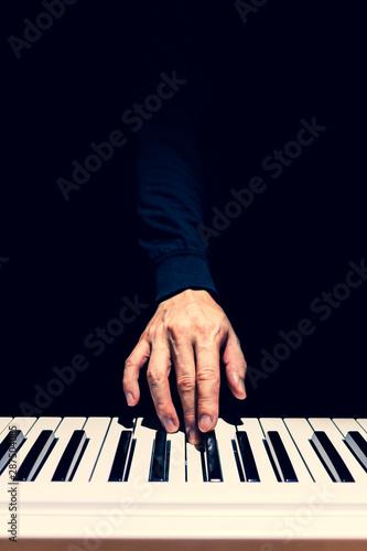 male musician hand playing on piano keys. music background Fototapeta