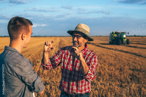 Fototapeta two ranchers talking on field. agricultural machine working in blurred background obraz