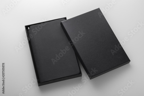 Fotografie, Obraz  Black notebook, pu leather cover, in box with pen holder, mockup on grey backgro