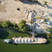 Crane Is Loading Sand And Gravel Onto Barge Ship For River Transport. Aerial Drone
