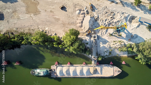 Vászonkép Crane is loading sand and gravel onto barge ship for river transport
