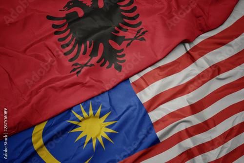 waving colorful flag of malaysia and national flag of albania. Wallpaper Mural