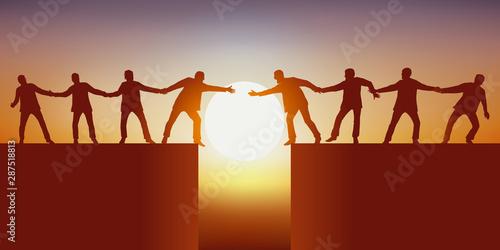 Fotomural Concept du travail d'équipe avec deux groupes d'hommes, séparés par un gouffre qui tente de se rejoindre en se tenant mutuellement pour réussir à surmonter l'obstacle