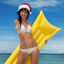 Happy Santa Woman With Inflatable Mattress In The Sea. Holliday Island Lifestyle. Vacation At Paradise. Ocean Beach Relax, Crystal-blue Sea Of Tropical Beach, Travel To Islands. Christmas Vacation