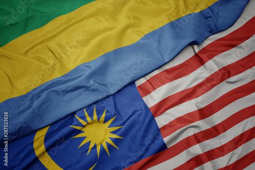 waving colorful flag of malaysia and national flag of gabon. Canvas Print