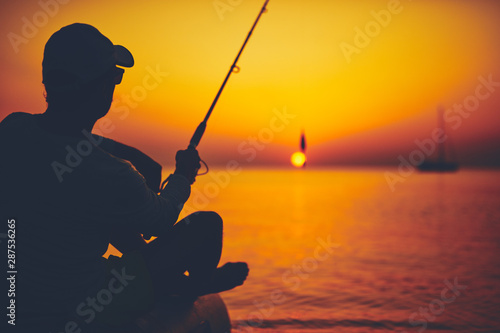 plakat Silhouette of a fisherman fishing in sunset time on the open sea.