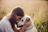 Fototapeta Zwierzęta - Girl and her friend dog on the straw field background. Beautiful young woman relaxed and carefree enjoying a summer sunset with her lovely dog