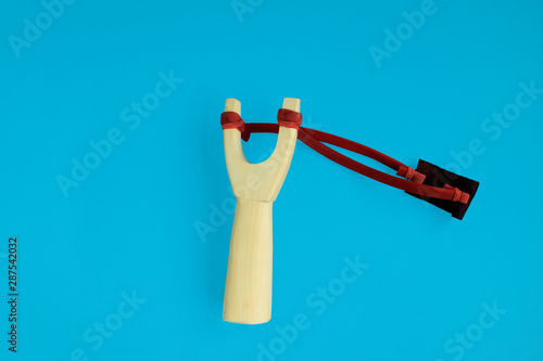 Handmade Y-shaped wooden stick with red elastic tied between top parts for child on blue background Wallpaper Mural