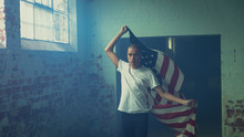 Young Man Holding An American Flag Inside An Empty Warehouse