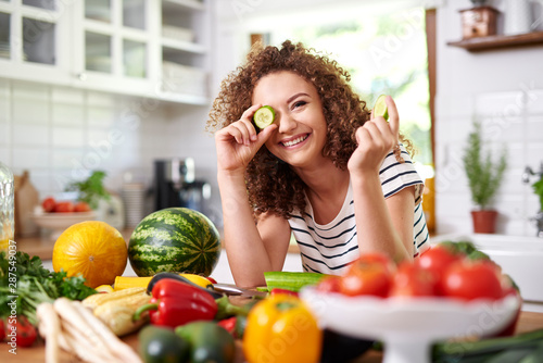 Woman holding a slice of cucumber