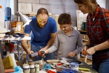 Family Tinkering Together In Workshop