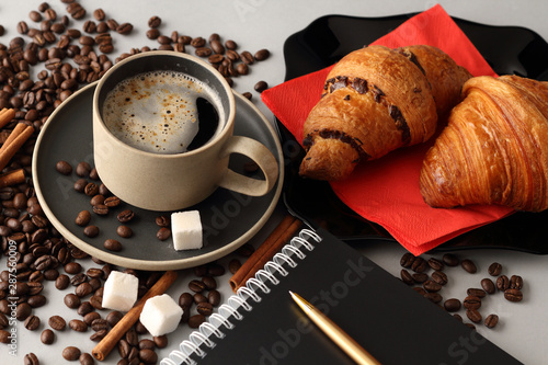 Tuinposter Cafe Morning coffee, croissants and a notebook with a pen
