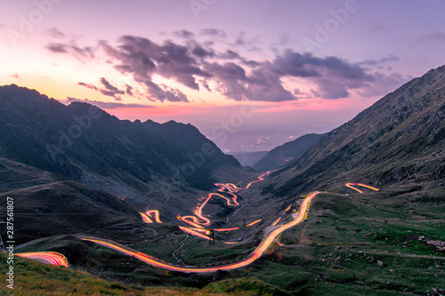 Photo Stands Black Long exposure with National Road 7C (DN7C), nicknamed Transfagarasan from the Fagaras mountains. The lights of the nostrils draw the path of the road. Photo taken on August 30th, 2019.