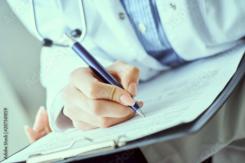 Female doctor hand hold silver pen filling patient history list at clipboard pad Canvas-taulu