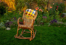 A Wicker Rocking Chair Sits On...