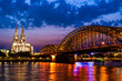 Beautiful night landscape of the Cologne, Germany with gothic cathedral, railway and pedestrian Hohenzollern Bridge and reflections over the River Rhine