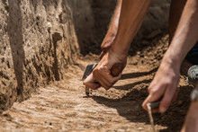 Archaeologists Excavating With Trowels