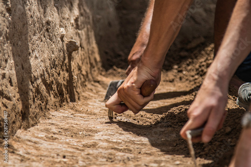 Photo Archaeologists excavating with trowels