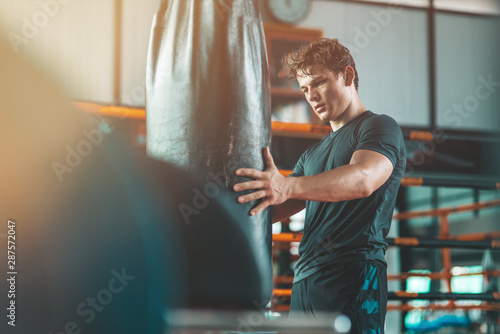 Portrait of young strong boxer standing in a gym near punch bag and looking at it Canvas Print