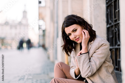 Street portrait of young beautiful happy smiling woman wearing stylish coat and pants. Model looking at camera. Female fashion concept. Copy space, free text