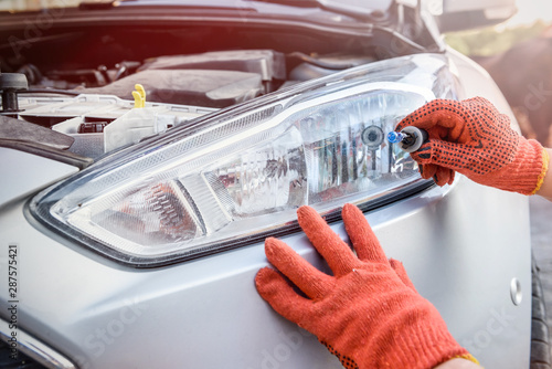 Obraz Mechanic holding lamp and cables from headlamp of car - fototapety do salonu