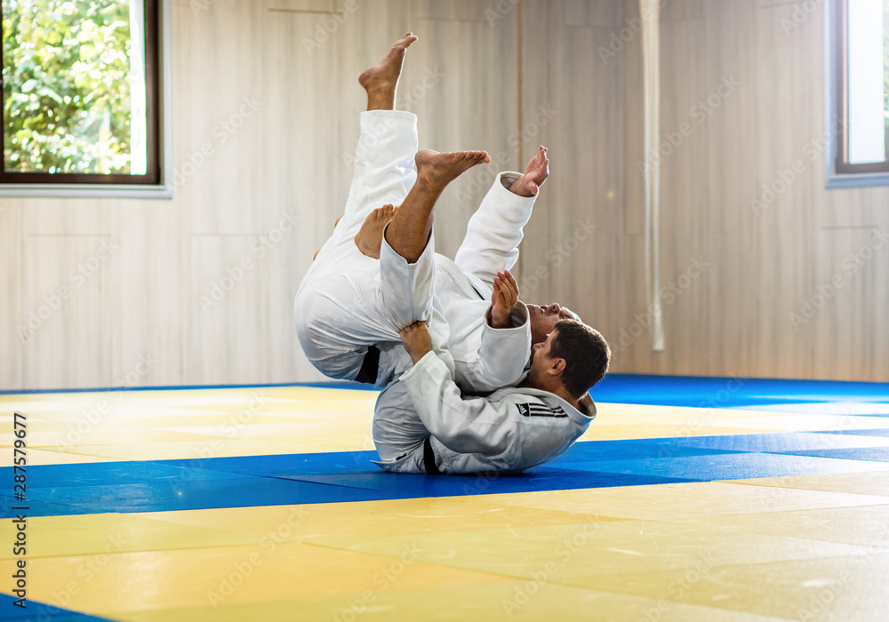 Fototapety, obrazy: Two adult man practicing judo in the sports hall.
