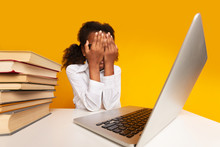 Schoolgirl Covering Face With Hands Sitting At Laptop In Studio
