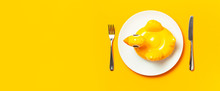 Inflatable Mini Yellow Chicken Or Duckling On White Plate, Fork Knife On Yellow Background. Creative Food Concept, Tobacco Chicken. Trend Inflatable Children Toy For Swimming. Layout For Design
