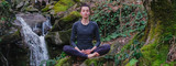Fototapeta Zwierzęta - Young slim woman practicing yoga outdoors in moss forest on background of waterfall. Unity with nature concept. Girl meditates sitting