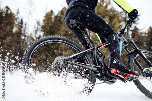 Papiers peints Glisse hiver Midsection of mountain biker riding in snow outdoors in winter.
