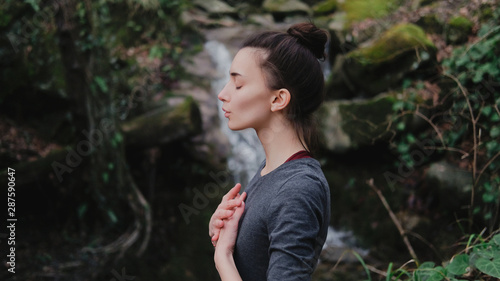 Young woman practicing breathing yoga pranayama outdoors in moss forest on background of waterfall Canvas Print
