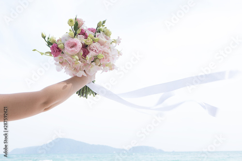 Photo sur Toile Les Textures View of woman's hand with bouquet on blue sea background