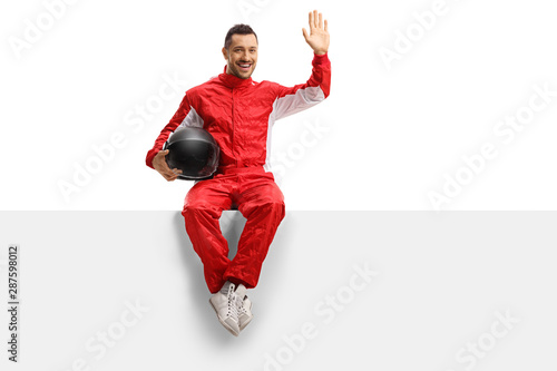 Young man racer in a red uniform sitting on a panel and waving