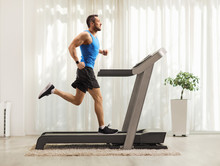 Young Man Running On A Treadmill At Home