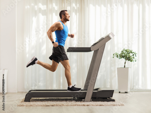 Cuadros en Lienzo Young man running on a treadmill at home