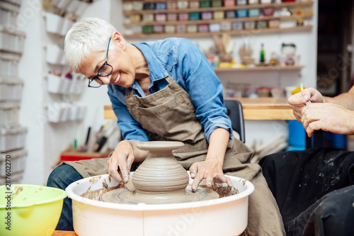 Fotomural  Senior woman spinning clay on a wheel with teacher at pottery class