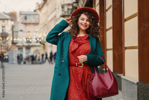 Happy smiling fashionable curvy woman wearing trendy autumn outfit: orange hat, snakeskin print dress, belt, green coat, holding red wicker leather bag, posing in street of European city Fototapet