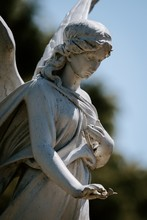 Vertical Shot Of A Female Angel Statue With A Blurred Background